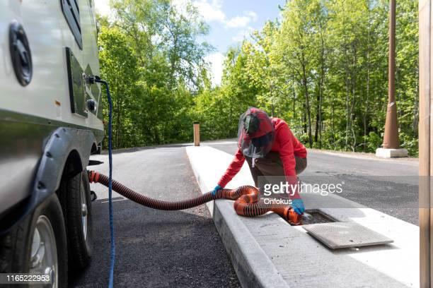 woman emptying rv sewer after camping - águas residuais imagens e fotografias de stock