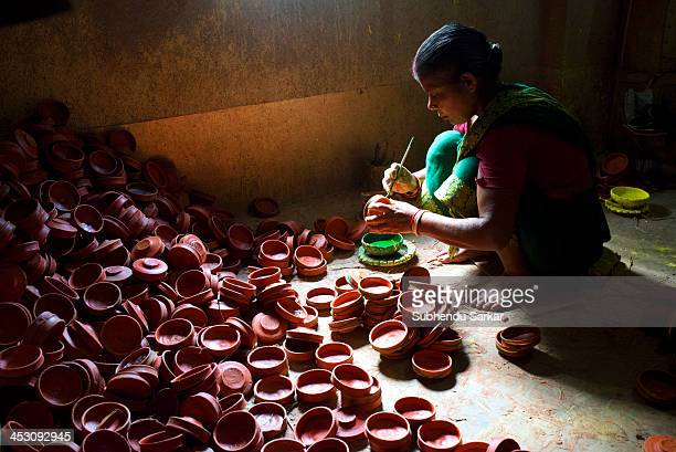 CONTENT] A woman engaged in colouring earthen pots in West Bengal India