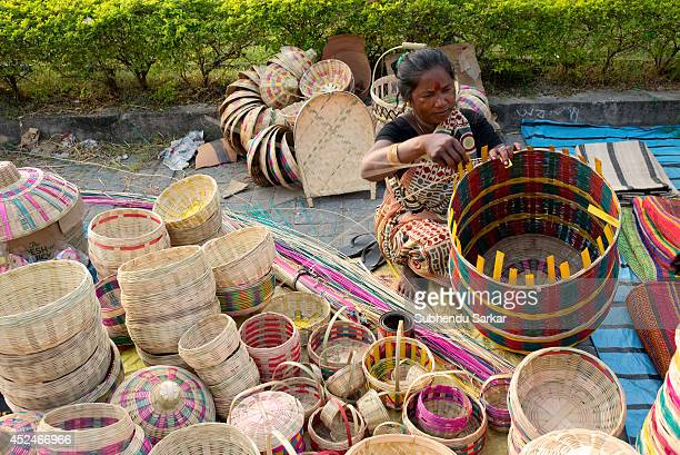 A woman engaged in making caneproducts Handicraft products of West Bengal are world famous Districts abound in artists making such products with the...