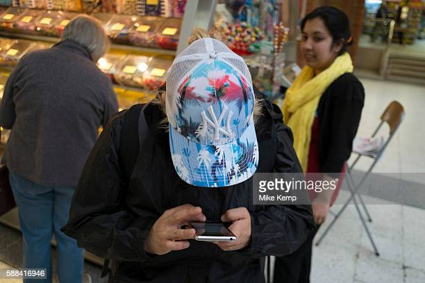 Woman engrossed in texting on her mobile phone in London England United Kingdom