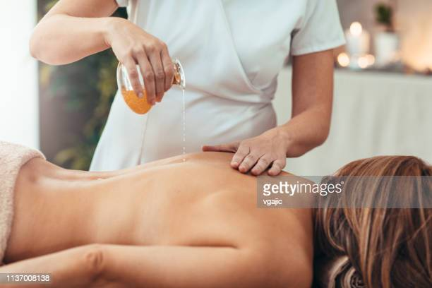 woman enjoy golden oil massage - essential oil stock pictures, royalty-free photos & images