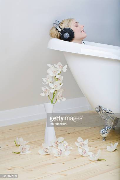 A woman enjoying a bath in a clawfoot tub, listening to headphones and singing along