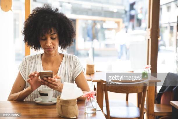 vrouw die van een onderbreking in een koffie geniet - afro amerikaanse etniciteit stockfoto's en -beelden