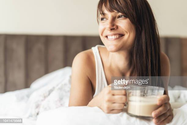 woman enjoying a cup of coffee in bed - waking up stock pictures, royalty-free photos & images