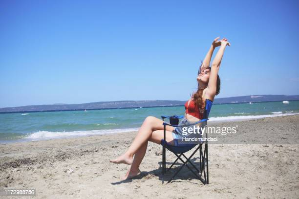 woman enjoying a day at the  beach - foldable stock pictures, royalty-free photos & images
