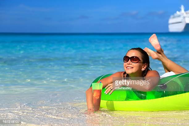 woman enjoying a drink on the beach