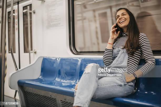 mulher que aprecia uma chamada de telefone ao viajar - trem do metrô - fotografias e filmes do acervo