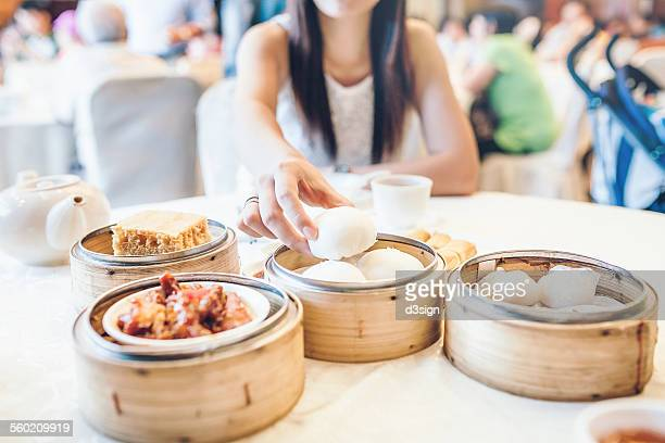 Woman enjoying a steamed bun and various dim sum