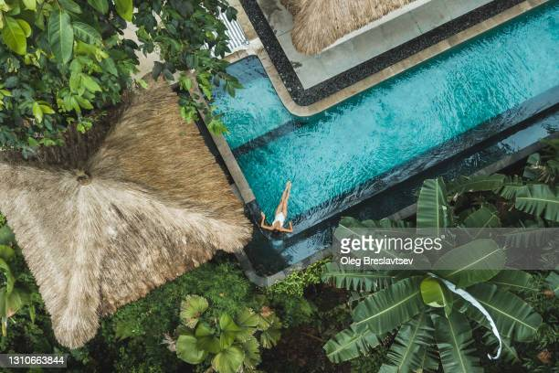 woman enjoying alone in luxury swimming pool, drone view from above - travel foto e immagini stock