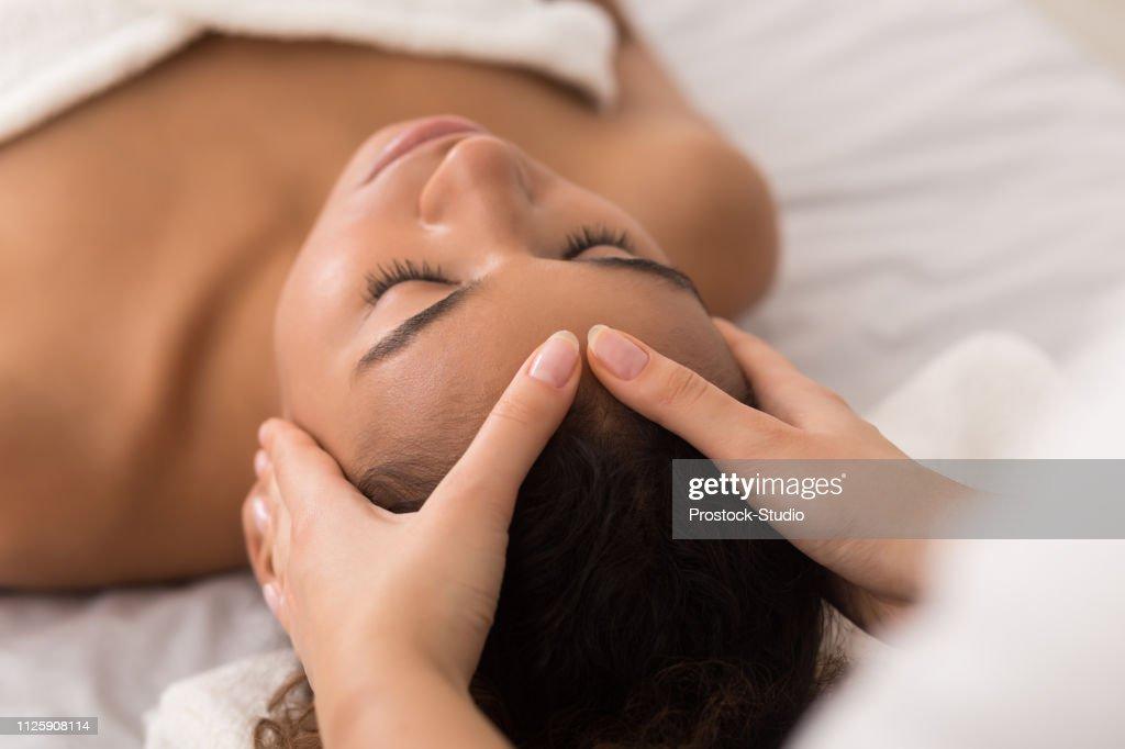 Woman enjoying anti aging facial massage in spa salon : Stock Photo