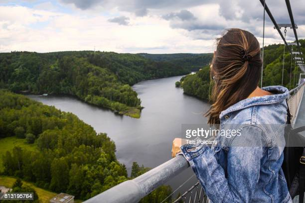 woman enjoying at the longest hanging bridge in the world, rappbodetalsperre, elbingerode harz, saxony anhalt, germany - saxony anhalt stock pictures, royalty-free photos & images