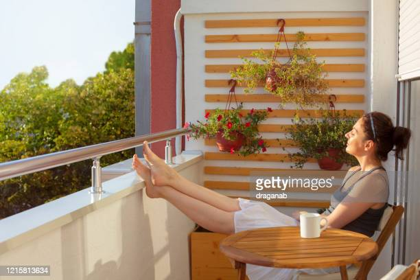 woman enjoying beautiful morning sun on her balcony - balcony stock pictures, royalty-free photos & images