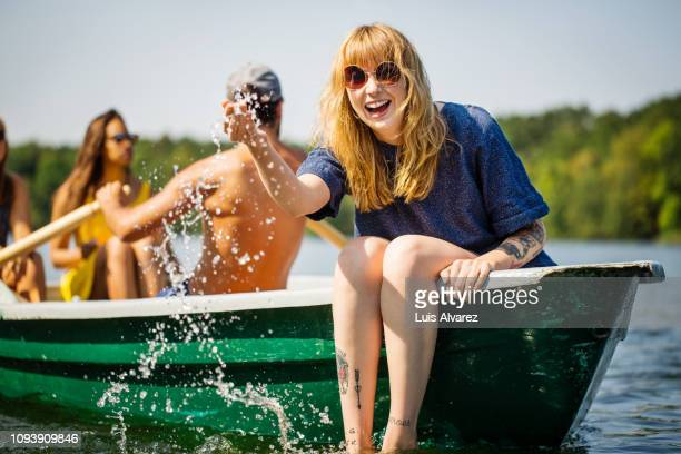 woman enjoying boat ride in lake - spaß stock-fotos und bilder