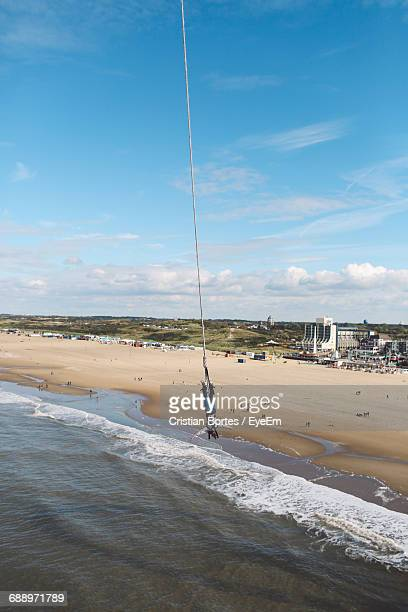 woman enjoying bungee jumping at beach - bortes foto e immagini stock
