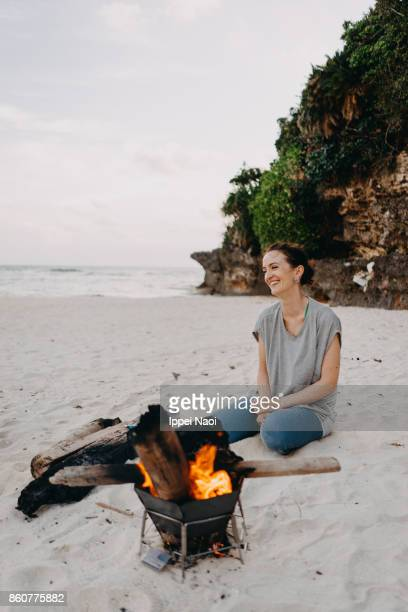 Woman enjoying campfire on beach, Japan