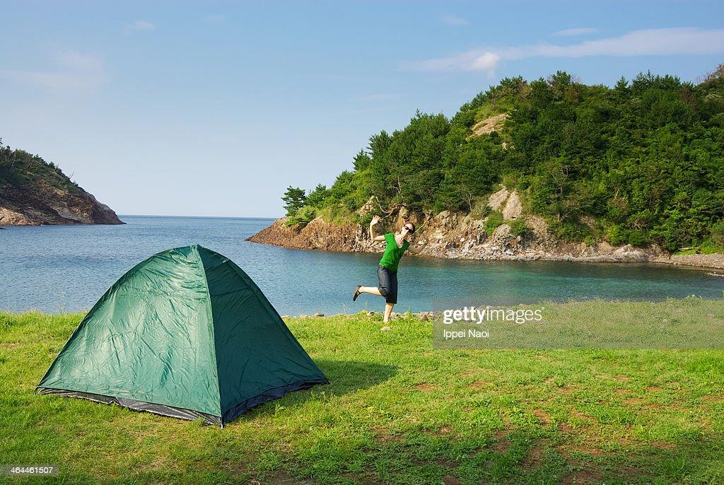 Woman enjoying camping by the sea : Stock Photo