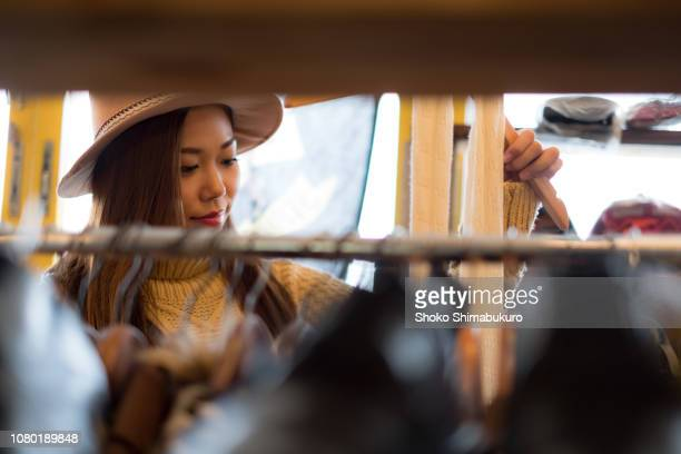 a woman enjoying casual clothes shopping in a clothing store. - boutique stock pictures, royalty-free photos & images