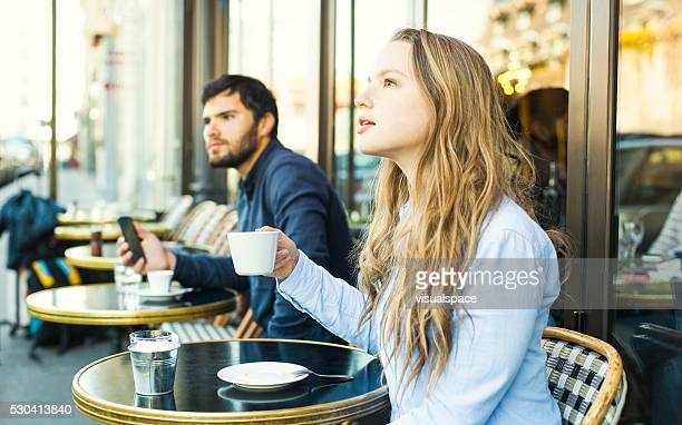 woman enjoying coffee in a cafe next to a stranger - stranger stock photos and pictures