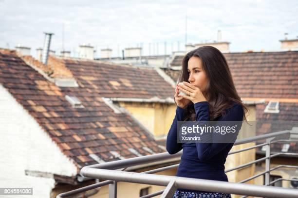 Mujer disfrutando de café en el balcón