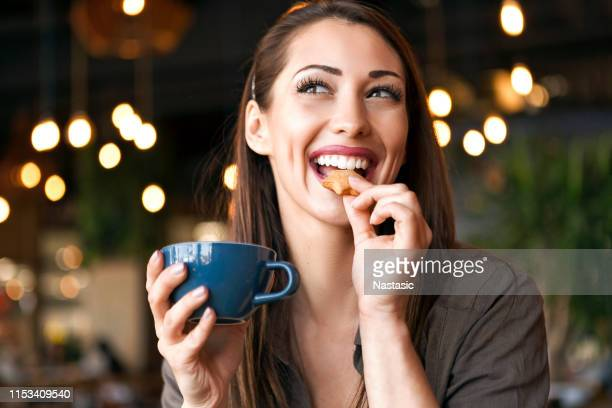 woman enjoying cookie with coffee in cafe place - cookie stock pictures, royalty-free photos & images