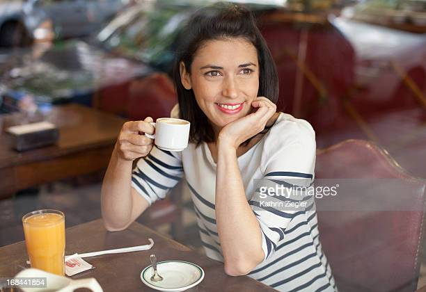 woman enjoying cup of coffee at a café