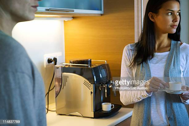 Woman enjoying cup of coffee in kitchen