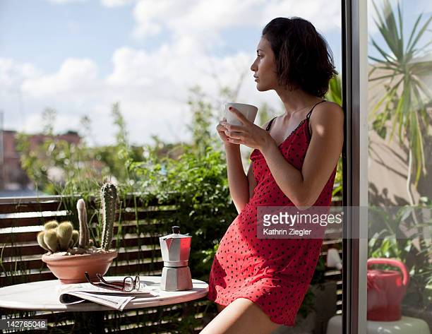 woman enjoying cup of coffee on the balcony