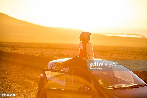 Woman enjoying desert roadtrip on the sunrise