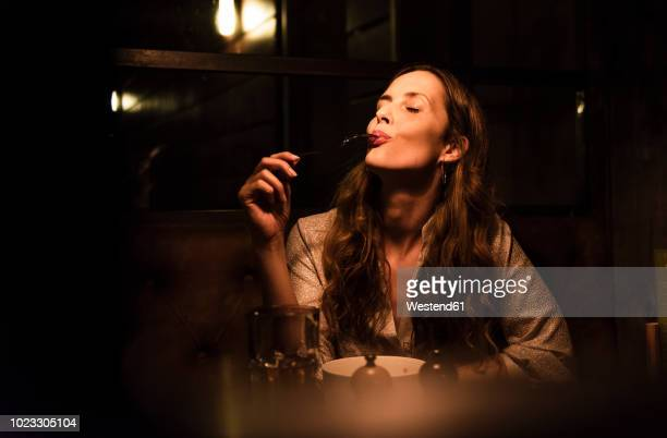 woman enjoying dinner - eten stockfoto's en -beelden