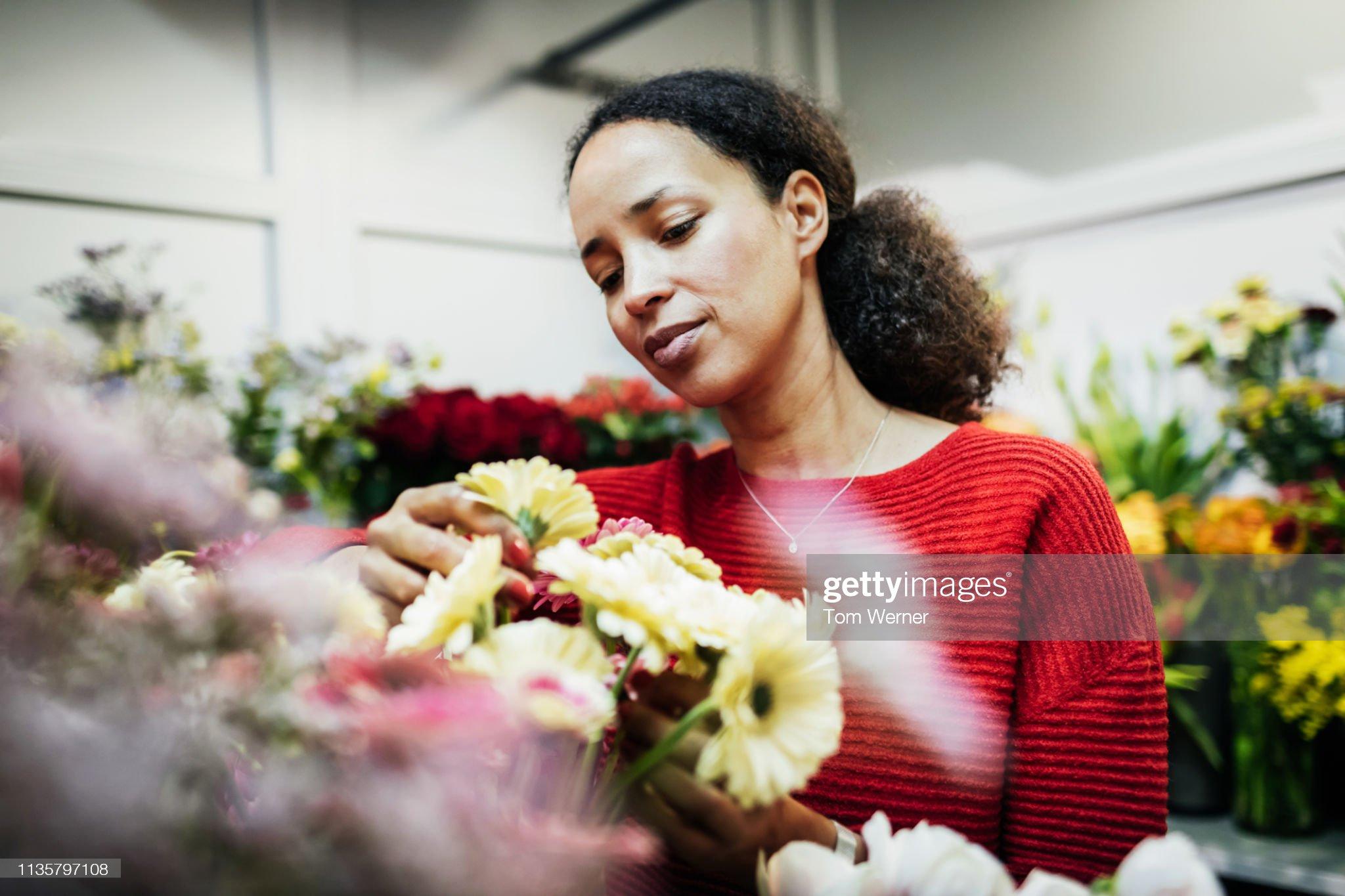 Woman Enjoying Display Of Flowers At Local Florist : Stock Photo
