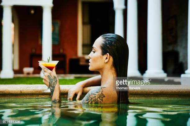 Woman enjoying drink while relaxing in pool at boutique hotel