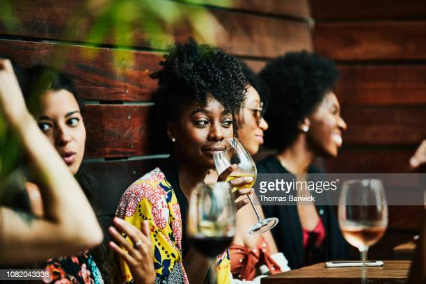 woman enjoying drink with friends at poolside bar - bere foto e immagini stock