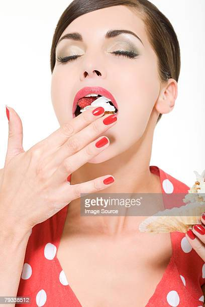 woman enjoying eating a cake - greed stock pictures, royalty-free photos & images