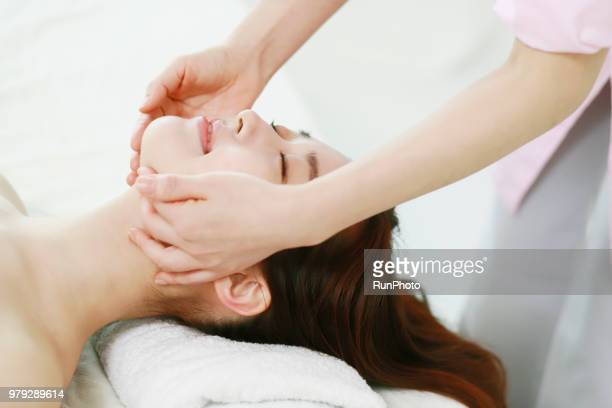 woman enjoying facial massage - body massage japan stock pictures, royalty-free photos & images