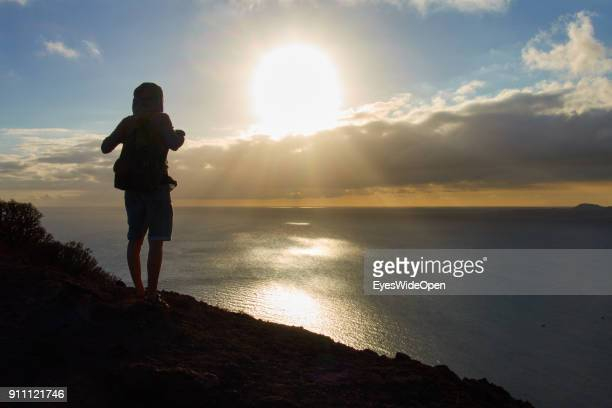 Woman enjoying freedom after climbing the Montana Roca with a panoramic view on the sandy beach of Playa del Medano on January 09 2018 in El Medano...