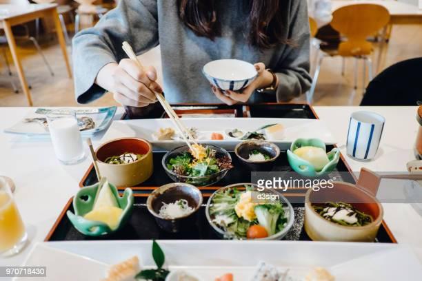 woman enjoying freshly made japanese style breakfast in a restaurant - japanische küche stock-fotos und bilder