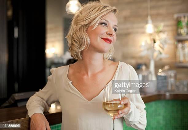 woman enjoying glass of white wine at the bar
