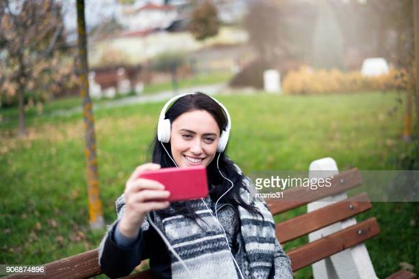 woman enjoying her coffee break at the park - phone cover stock pictures, royalty-free photos & images
