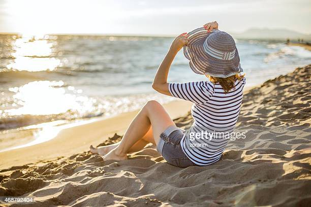woman enjoying her day off at the beach - sun hat stock pictures, royalty-free photos & images