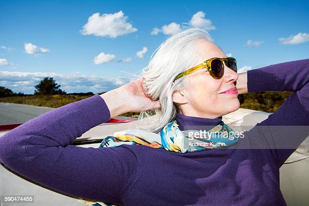 woman enjoying her ride in a convertible. - white hair stock pictures, royalty-free photos & images