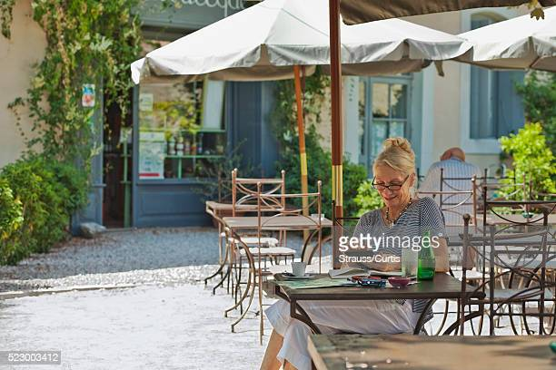 woman enjoying her tablet reader while seated in outdoor cafe. - pavement cafe stock pictures, royalty-free photos & images