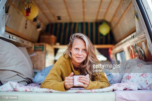 woman enjoying hot drink in bed in camper van - 腹ばい ストックフォトと画像