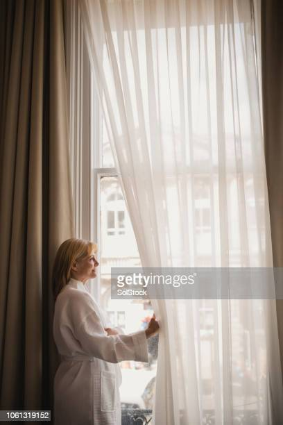 woman enjoying hotel room view - sheer fabric stock pictures, royalty-free photos & images