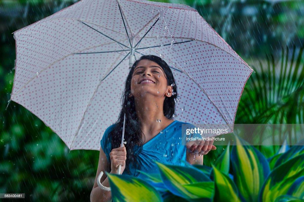 Woman enjoying in the rain : Stock Photo