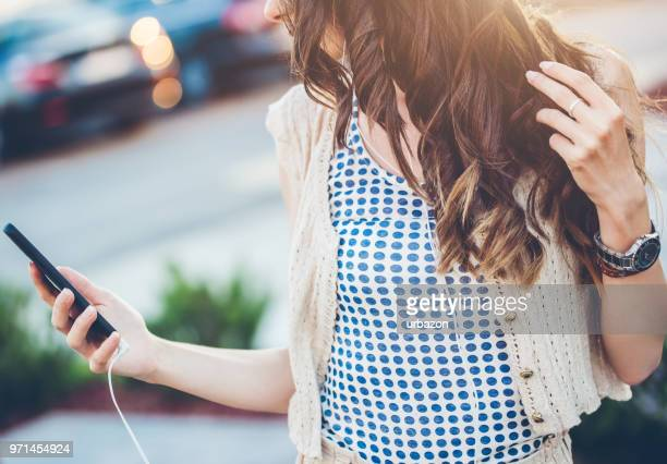 woman enjoying in walking with headset and mobile phone. - wavy hair stock pictures, royalty-free photos & images