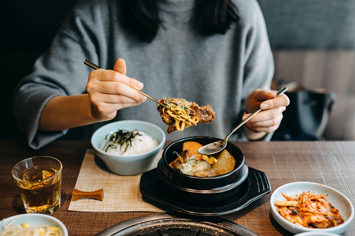 Woman enjoying Korean cuisine with a variation of traditional dishes in a restaurant - gettyimageskorea