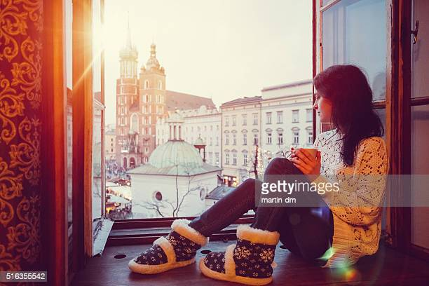 Woman enjoying Krakow city from the window