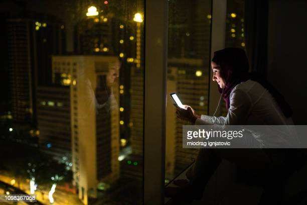 woman enjoying listening to music late at night - muslim woman darkness stock photos and pictures