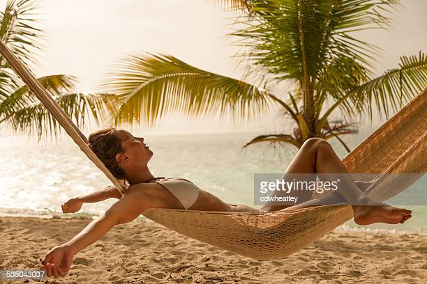 woman enjoying little rain while relaxing in a beach hammock