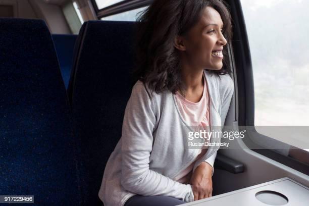 Femme appréciant regardant par la fenêtre du train.